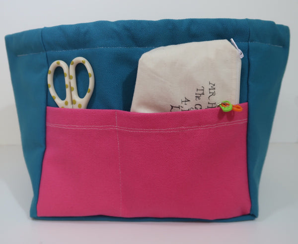 Canvas Cube Knitting Project Bag with Pockets, large size for sweaters and blankets. Cube shaped drawstring bag, Teal coloured with outside pink pockets with items shown in pockets