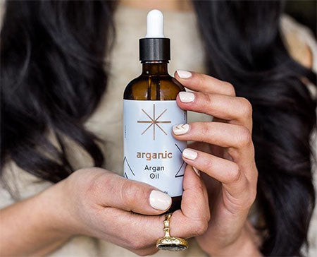 Image of a lady holding a bottle of our Cosmetic Argan Oil from Morocco