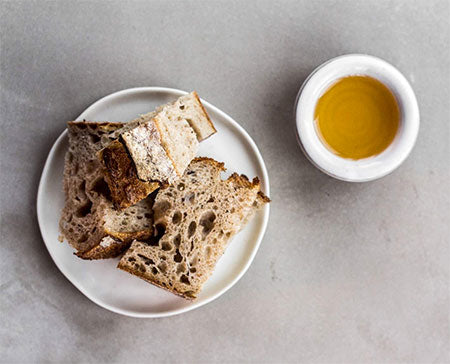 Picture of our Moroccan Argan Oil set in a bowl alongside a lightly toasted slice of bread