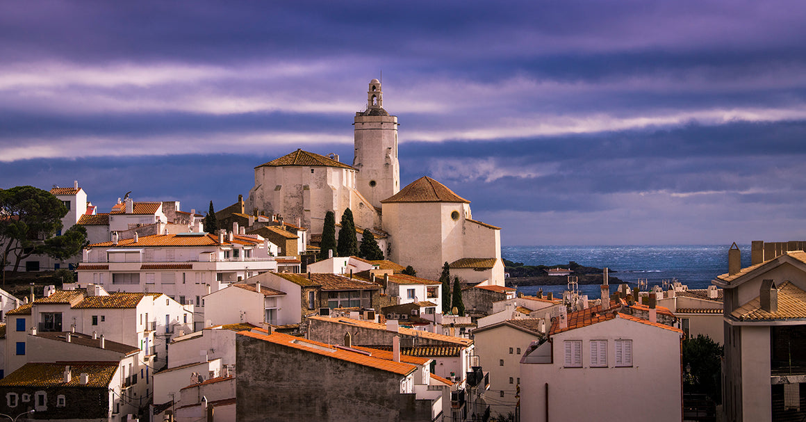 Cloudy purple evening sky photographed atop Spanish city rooftops thumbnail