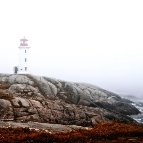 A white light house on a slightly foggy day