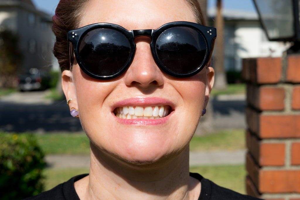smiling with teeth and sunglasses in sun