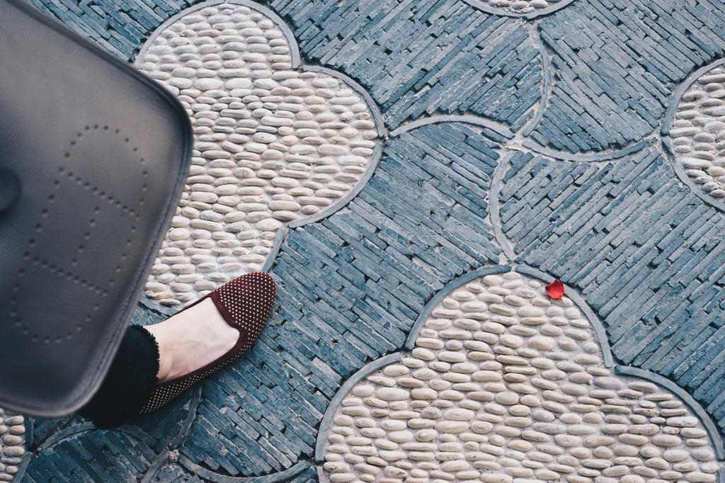 Chinese paved trefoil shaped stone floor with red loafer and purse in frame