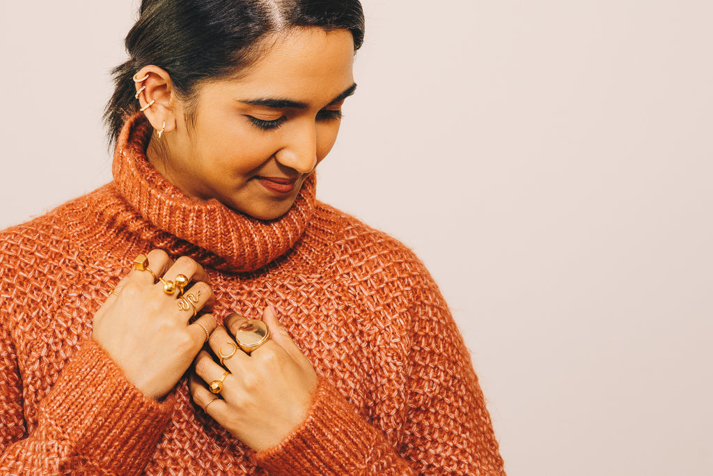 girl in orange turtleneck sweater with gold jewelry