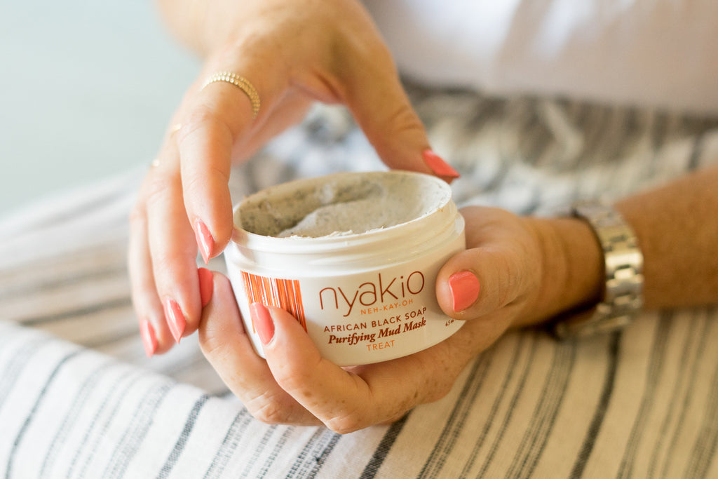 hands holding nyakio African black soap mud mask