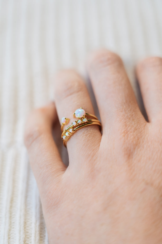 opal stacking ring and gold stacking rings on hand