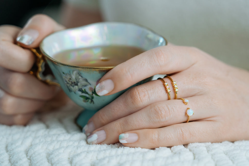 hands holding vintage tea cup with nail art and rings by Janna Conner