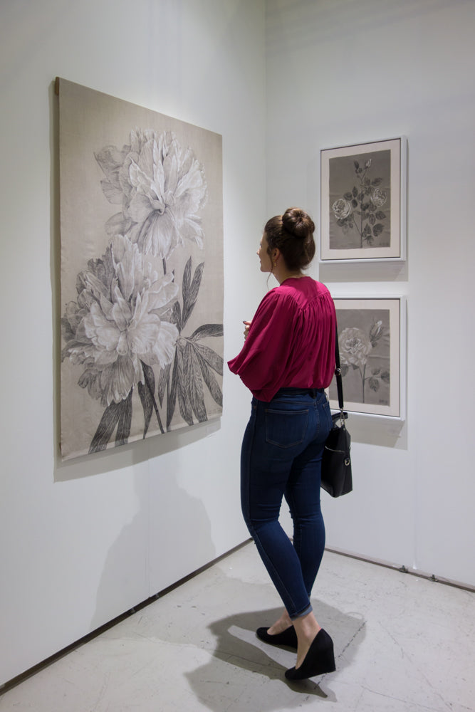 girl looking at charcoal peony flowers on Belgian linen other art fair Emily Morgan Brown