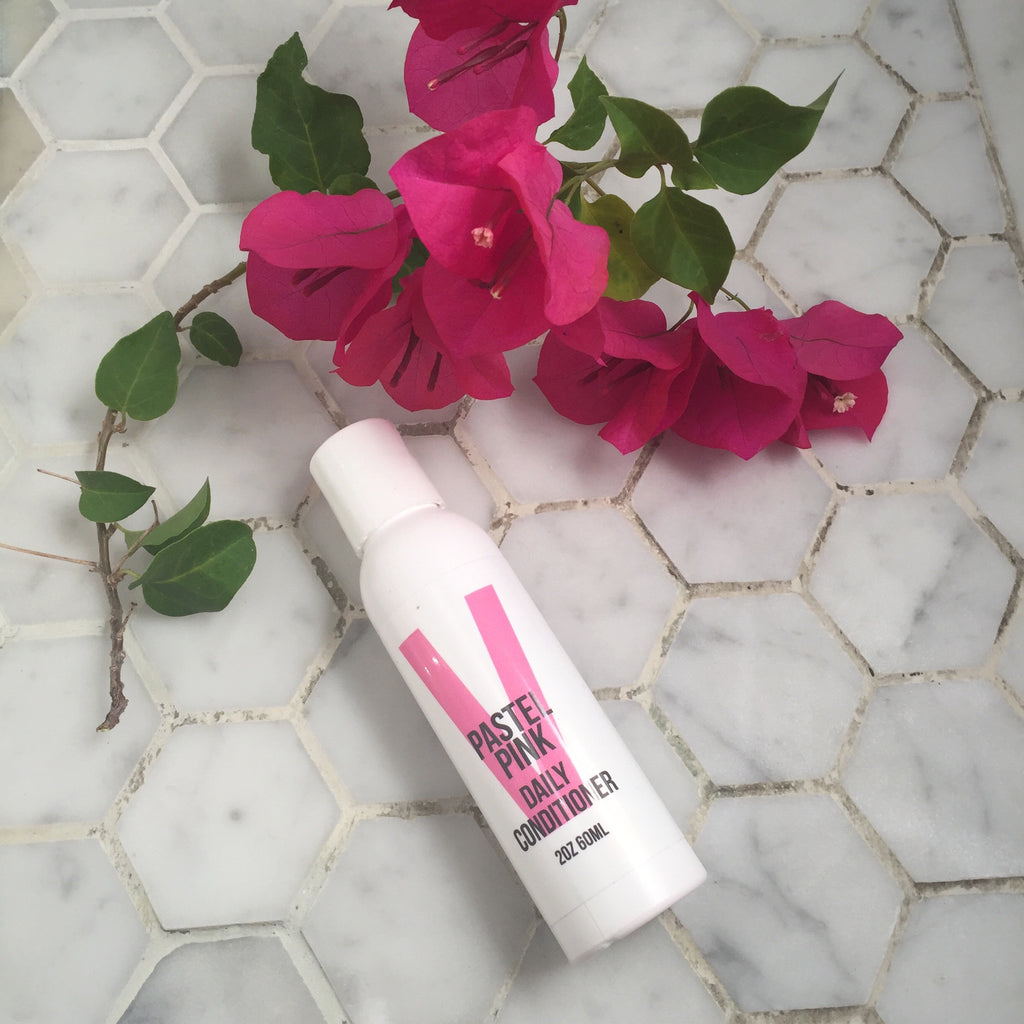 overtone pastel pink daily conditioner with bougainvillea on white tile floor