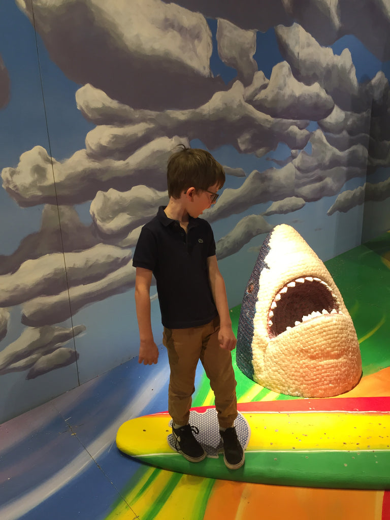 boy on surfboard with shark in candy at candytopia