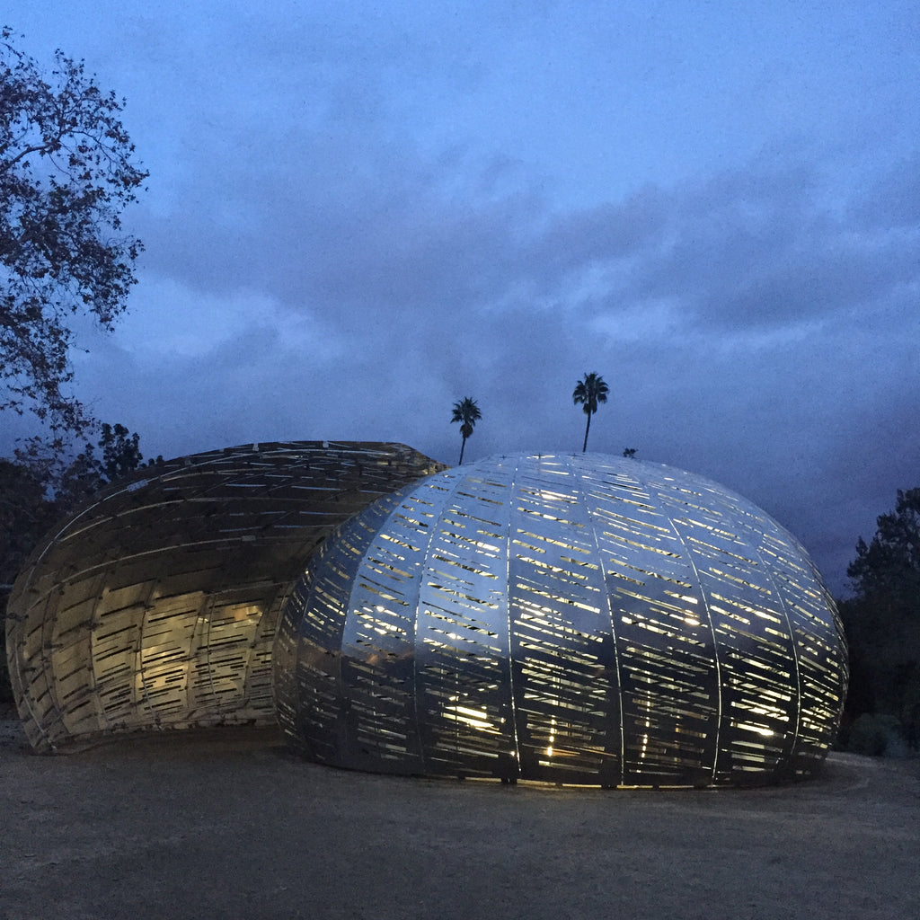 silver metal nautilus shaped Orbit Pavilion at night with palm trees