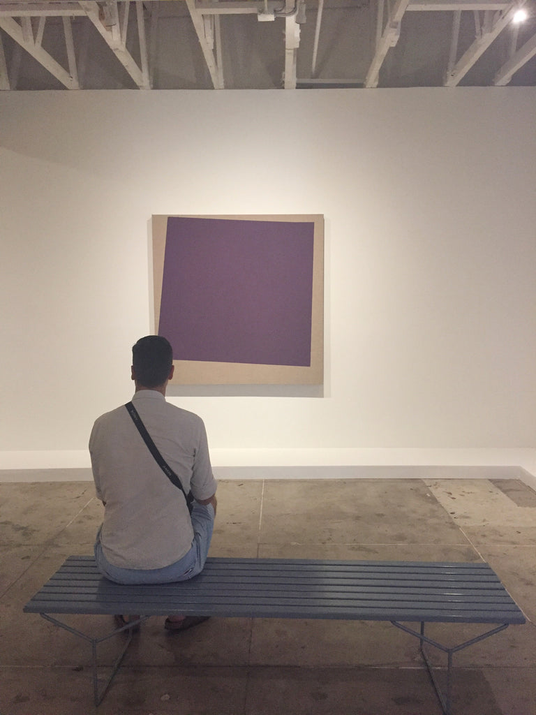 man sitting and looking at Noah Davis purple square painting at Underground Museum LA