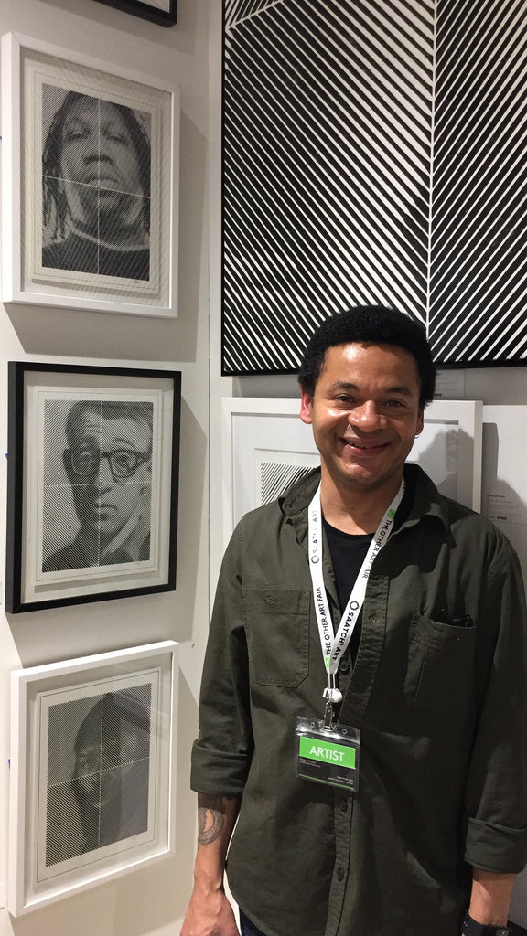 Michael o'neal artist in front of drawings of woody Allen and Krs-one at the other art show la