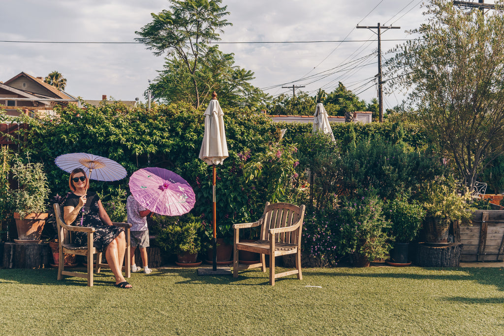 Janna Conner and son with parasol in purple garden at Underground Museum LA