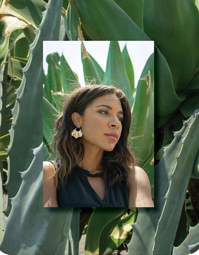 Gold wavy hoop earrings on model with green cactus background
