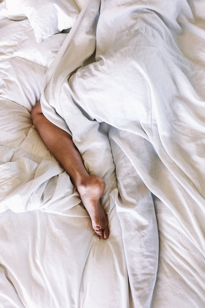 woman's leg in bed white sheets