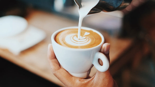 latte in hand with milk pouring over cup