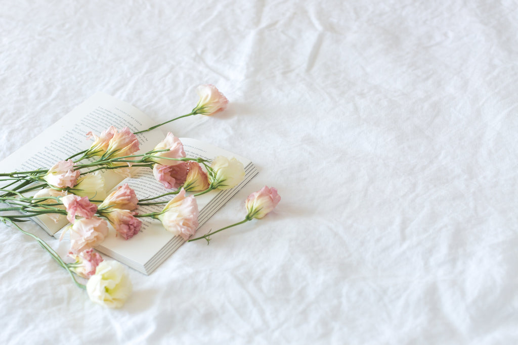 Pink flowers spread on a bedsheet with a book