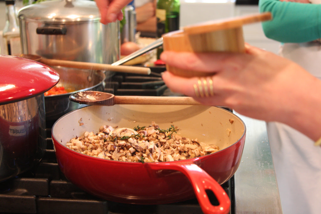 hand stirring pot of stuffing on stovetop