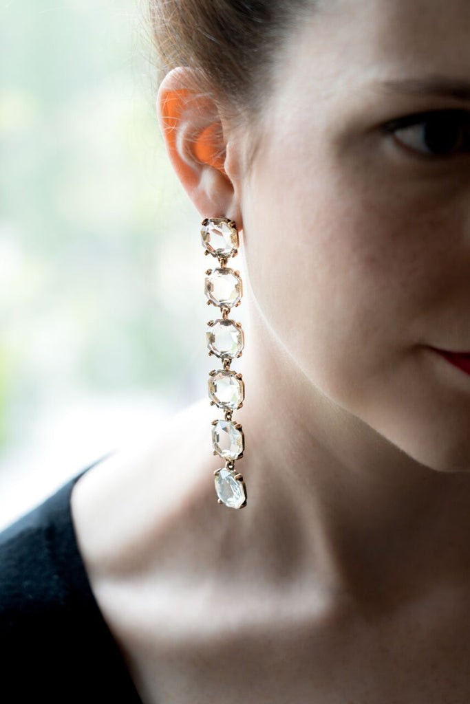 model wearing long shoulder duster crystal drop earrings backlit