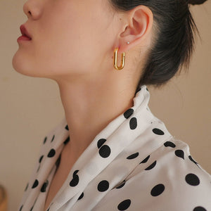 gold rectangular huggie hoop earrings on model