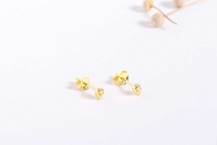 gold skull stud earrings front