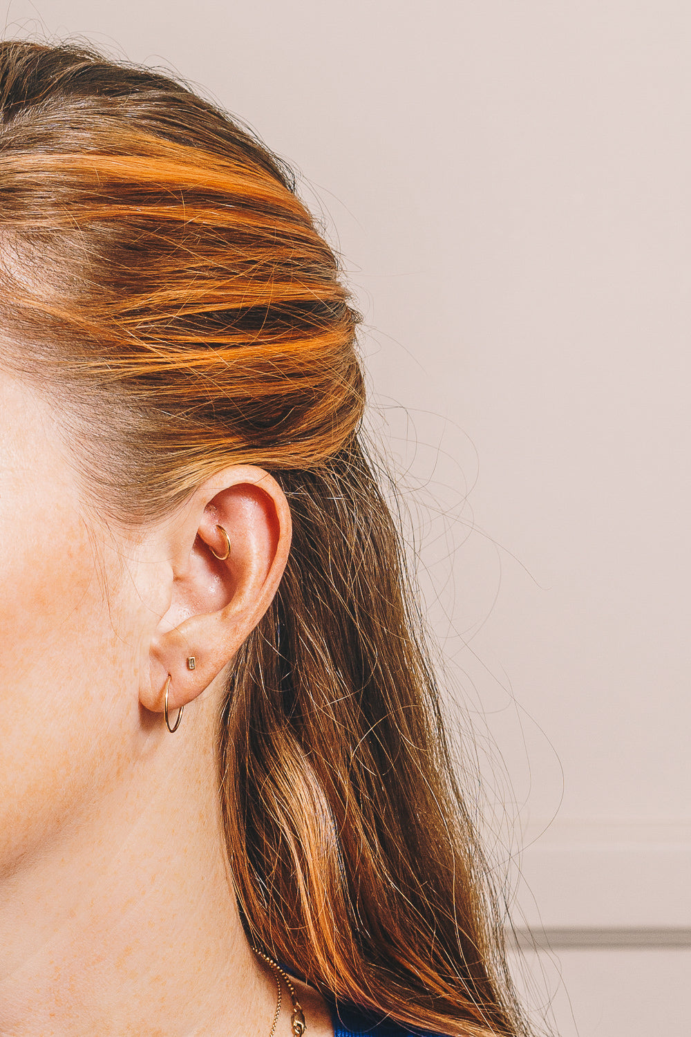 14k gold hoops on model with diamond baguette stud earring