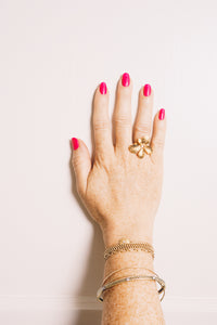gold flower ring on model hand with stacking bracelets