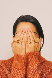 gold stacking rings on model hands in face
