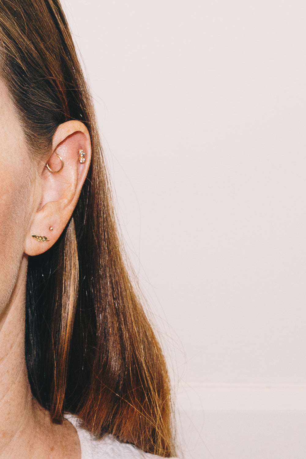 14k gold leaf earrings on model with rook and helix piercings