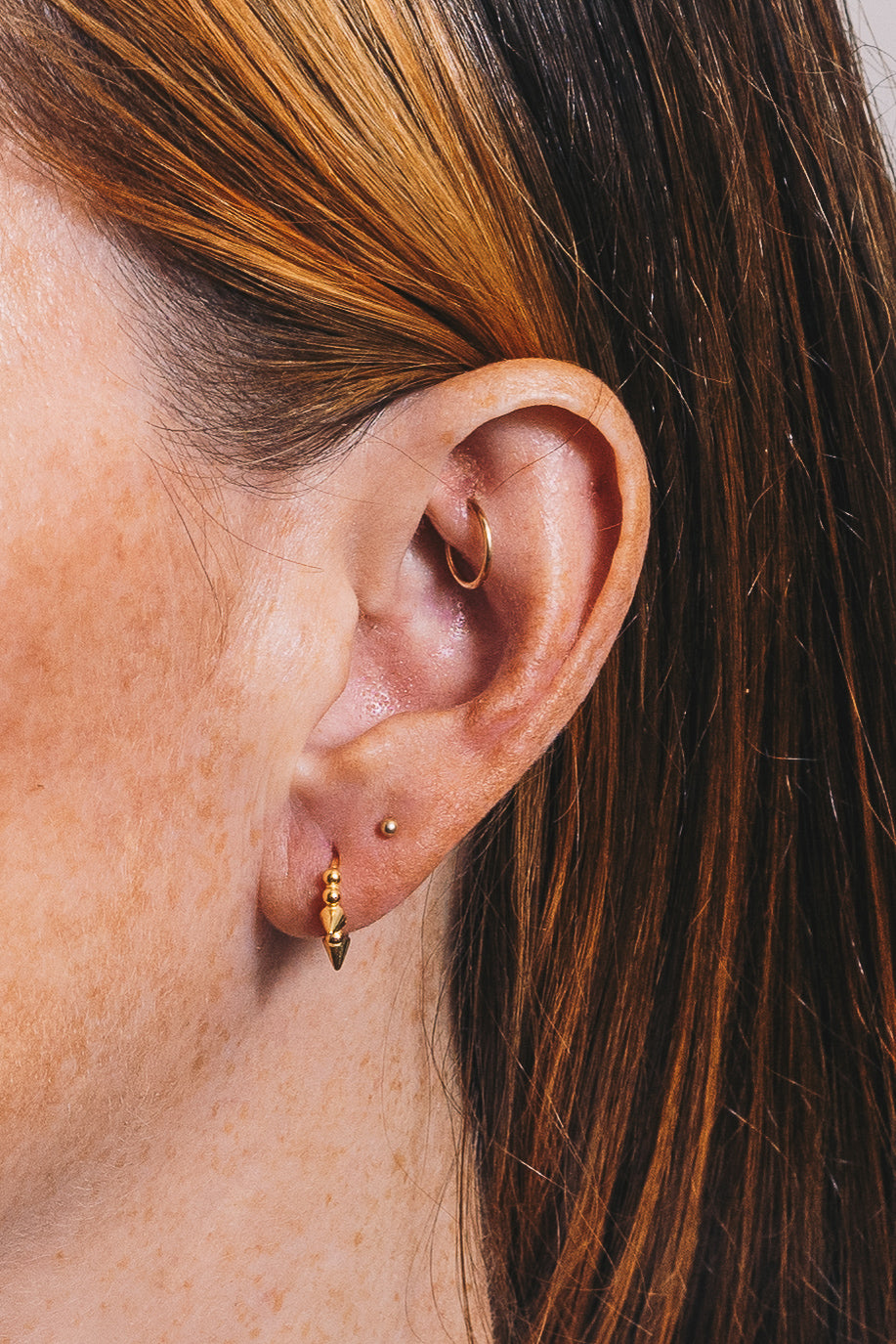 gold spike huggie hoop closeup on ear
