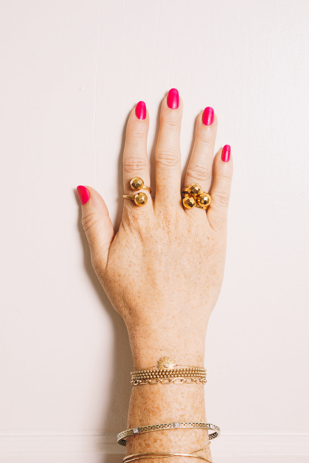 gold disco ball wraparound ring and gold stacking rings on hand