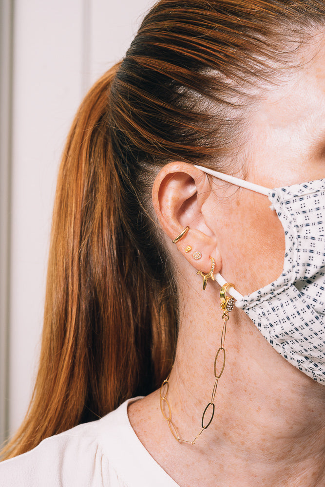 gold paperclip mask chain on model with multiple piercings
