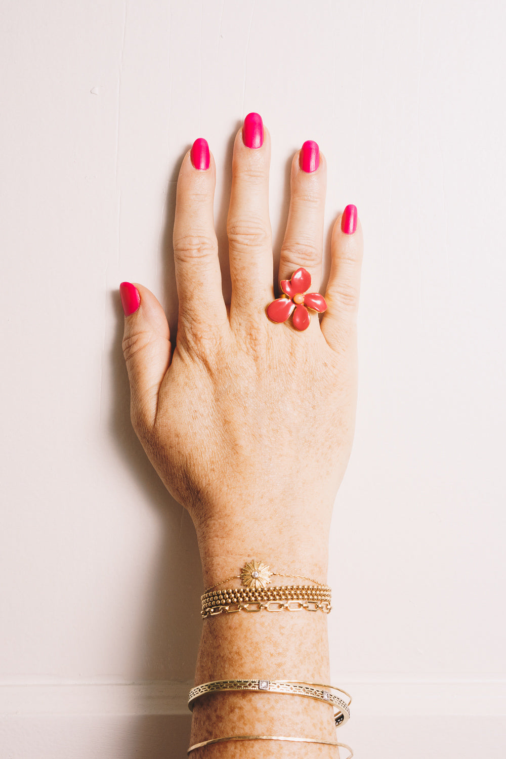 gold enamel flower ring on model hand with stacking bracelets