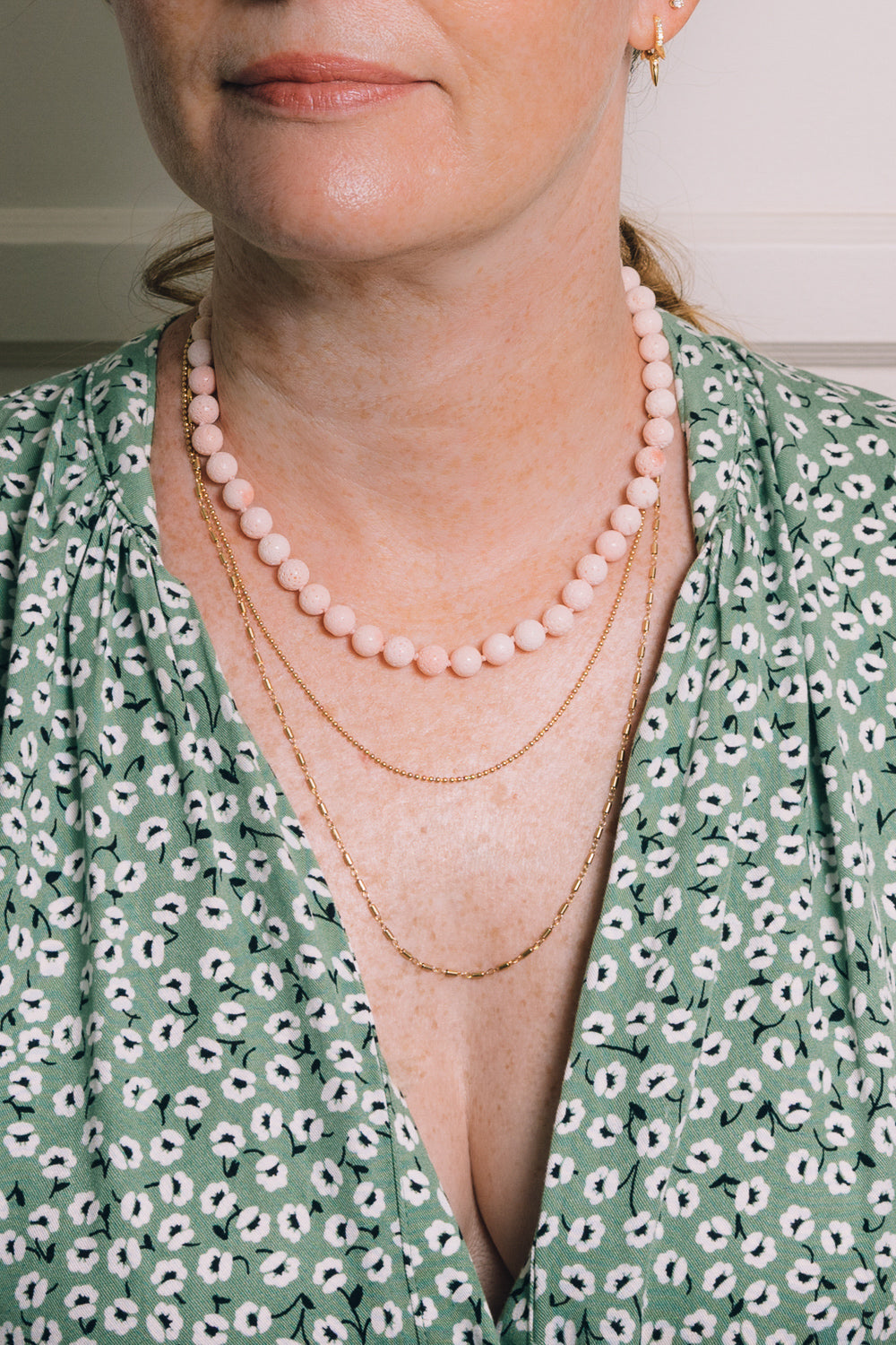 salmon sponge coral beaded necklace with layering necklaces on model
