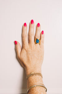 blue teardrop gold cigar band ring on hand