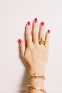 gold starfish ring with coral cabochon on model hand
