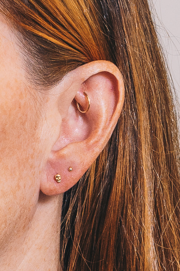 tiny gold skull stud earring with multiple piercing ideas