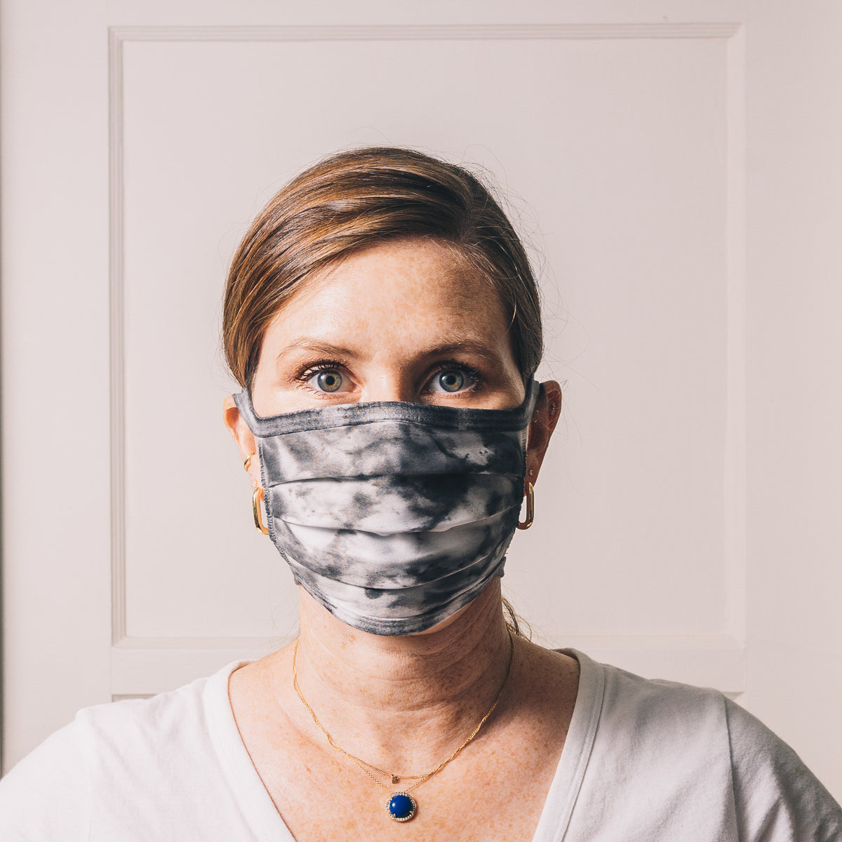 black and white tie dye reusable adjustable face mask on model