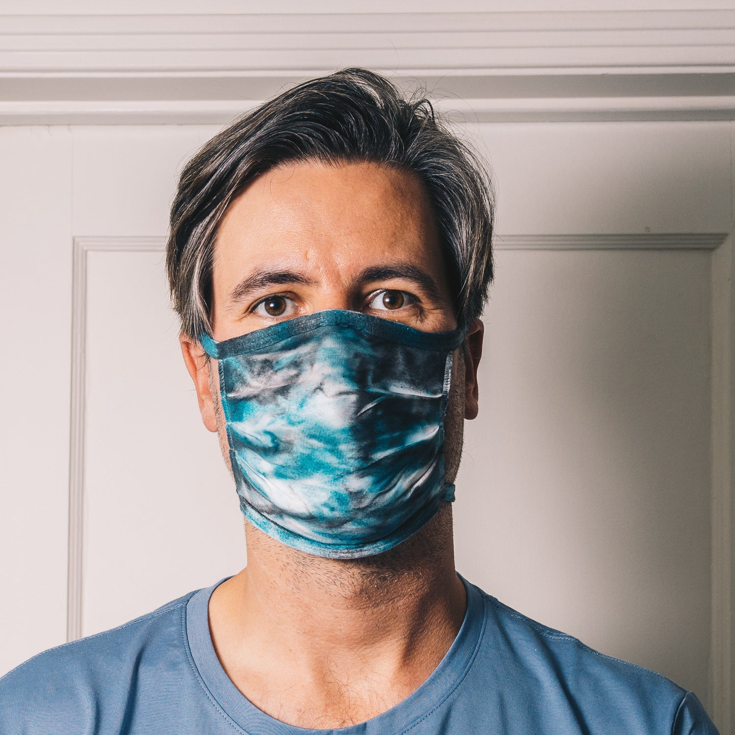 teal and black tie dye reusable adjustable face mask on male model