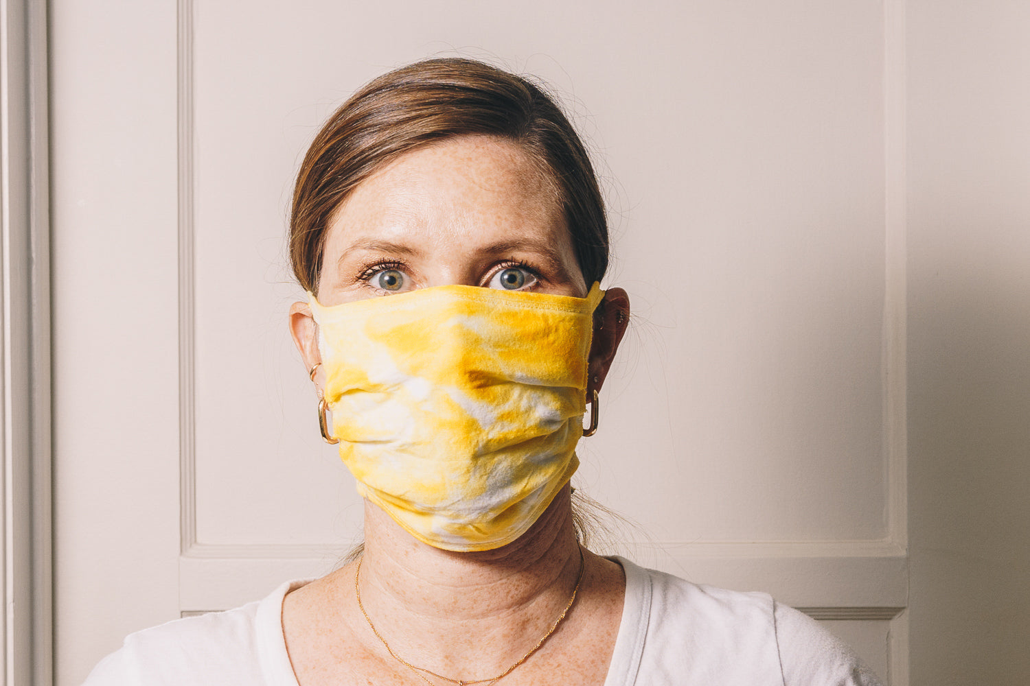 yellow tie dye reusable adjustable face mask on model