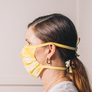 yellow tie dye reusable adjustable face mask on model side profile