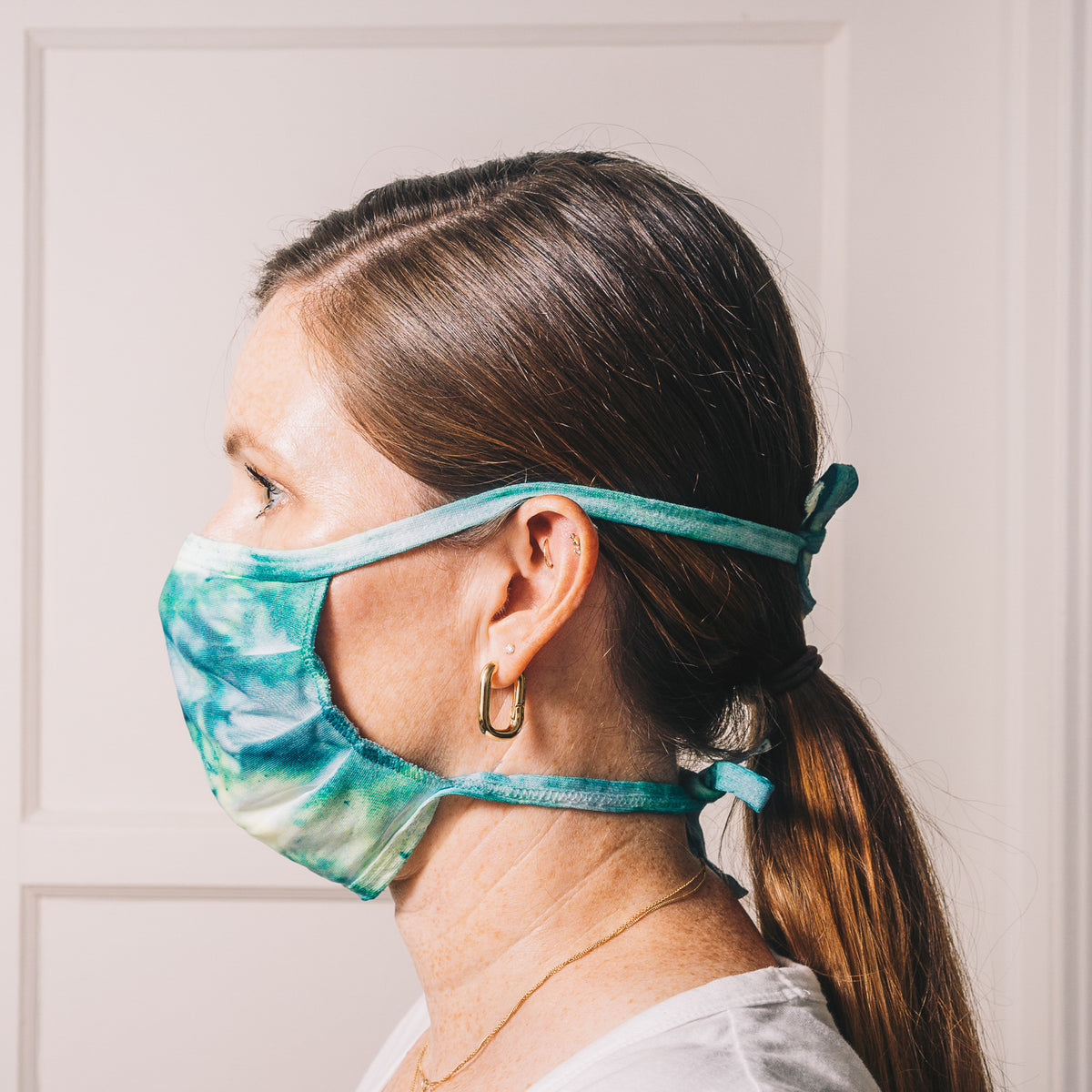 tie dye reusable adjustable face mask on model side profile