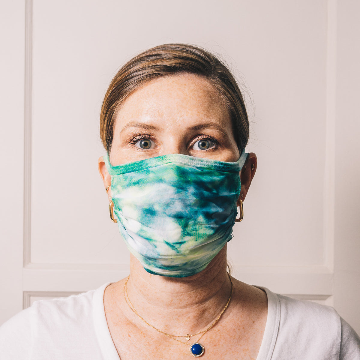 teal and neon green tie dye reusable adjustable face mask on model