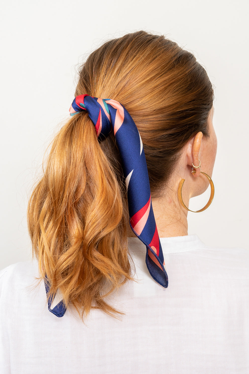 red head with blue and red print scarf tied in hair ponytail hoop earrings Janna Conne