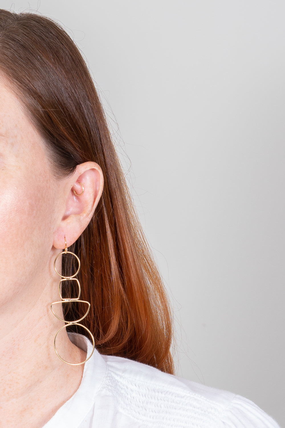 gold wire cutout geometric earrings on red haired model