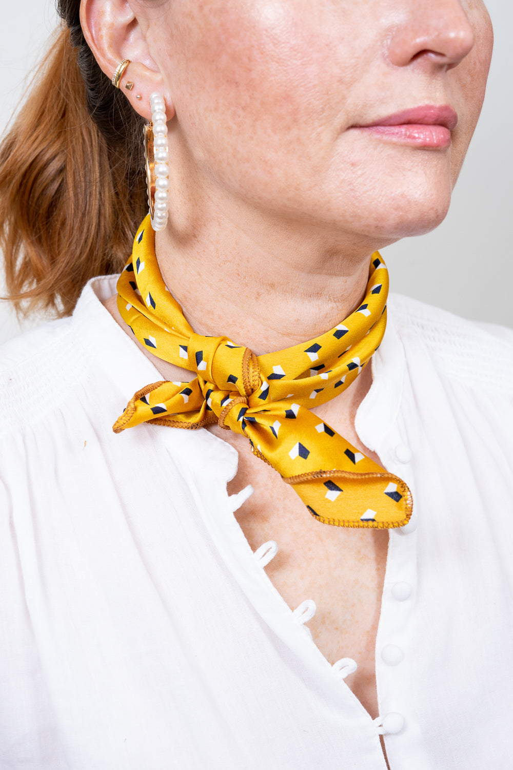 yellow print neck scarf tied around model neck Janna Conner