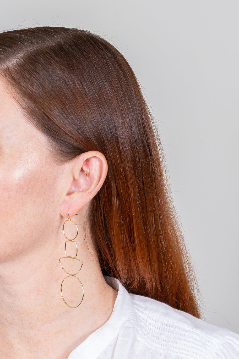 gold wire cutout geometric earrings on red hair model