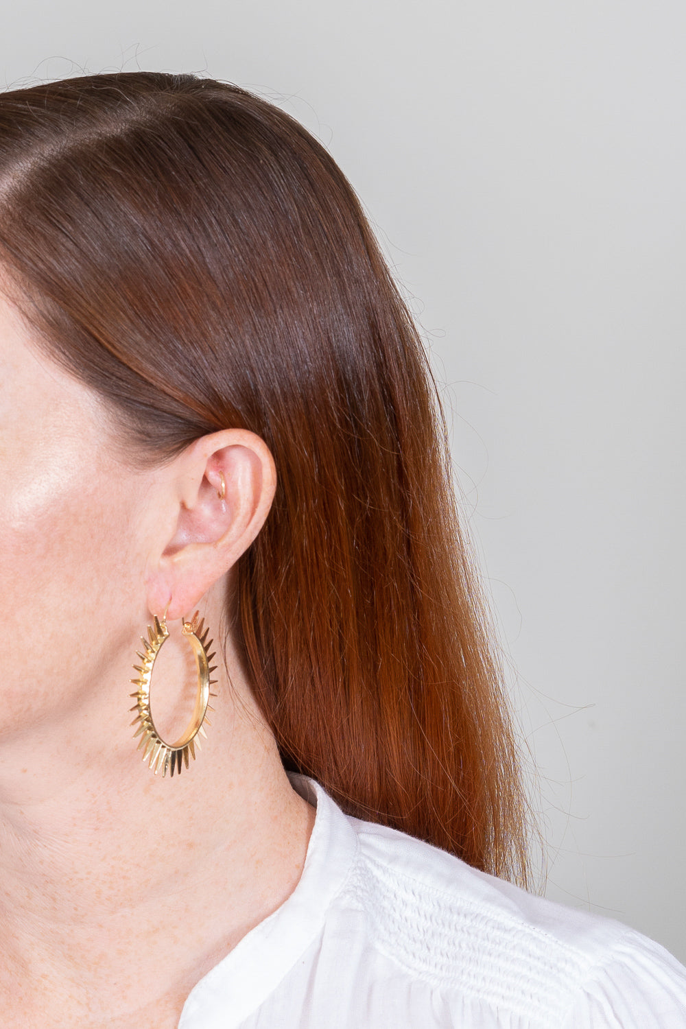 large gold spike basket hoop earrings on red hair model