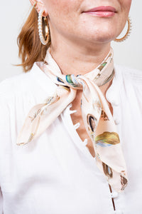 model wearing pale feather print neutral neck scarf pearl hoop earrings janna conner